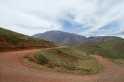 The curved dirt road in the mountains. View of the rural route curve along the hills and green valley.