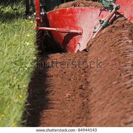 The curved mouldboard of a plough and the resulting furrow.