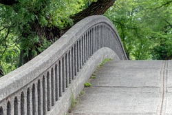 The curved slopes and handrail of a concrete bridge in the park.
