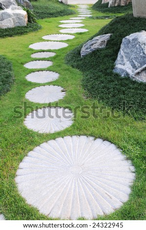 The curving stepping stone footpath in the landscape garden. - stock photo
