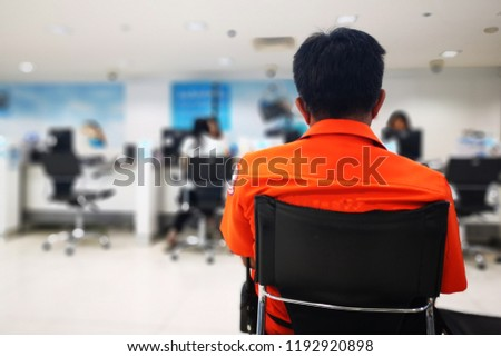 The customer is wearing a orange shirt waiting for service from the staff. Background blurred the staff. Selected focus, copy space. #1192920898