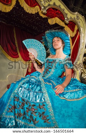 The cute girl in blue old-fashioned dress and hat sits in a carriage