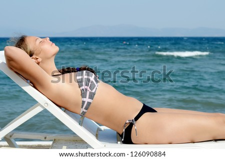 The cute girl on a plank bed at the sea