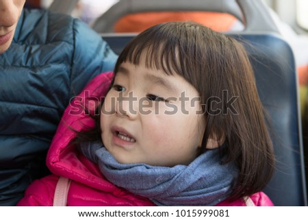 The cute little asian girl is sitting on the bus #1015999081