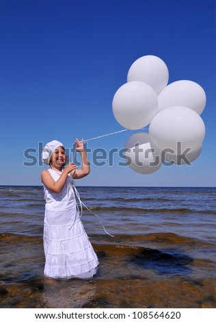 The cute little blonde girl in a white dresses with white balloons on the beach