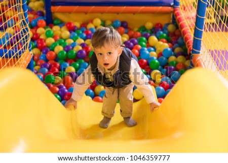 The cute little boy playing in the game room and getting on the hill #1046359777