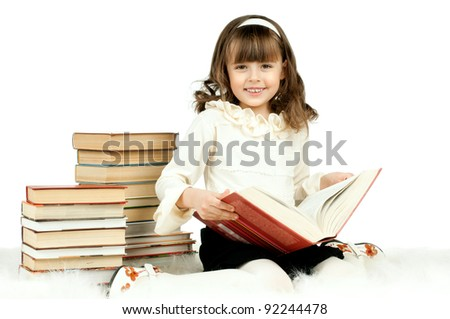 the cute little girl lie with textbook and happy smile, on white background, isolated