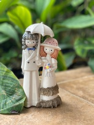 The cute statue couple with The dominant clothing design is white