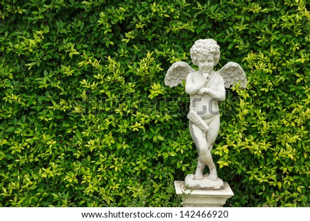 the cute statue in green garden
