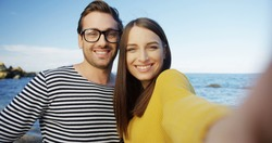 The cute young woman and man taking funny selfies and grimacing on the seacoast. Outdoors. POV. Close up. Portrait shot