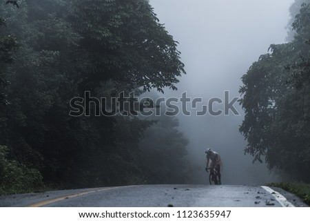 The cyclists ride his bicycle up high on hill, Cycling to destination no matter how bad weather is. Foggy, windy, raining and cold day.