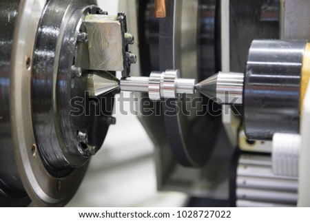 The cylindrical grinding machine with the steel shaft.Hi precision manufacturing concept.