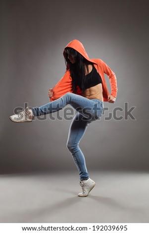 The dancer in a hood. Female dancer posing standing on one leg. Full length studio shot on gray background.