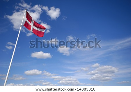 The danish flag and blue and cloudy sky