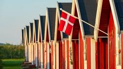The Danish flag Dannebrog and red fishing huts on the baltic sea coast