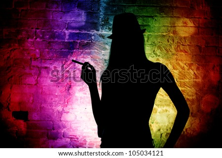 The dark silhouette of an elegant woman in a man's hat against a brick wall. Night club.