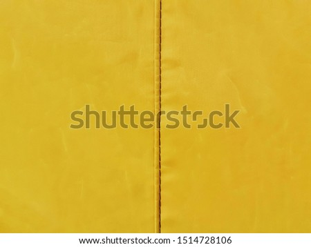 The dark yellow canvas surface and the seam edge of the sewing line are vertical, center vertical. Used for an abstract background.