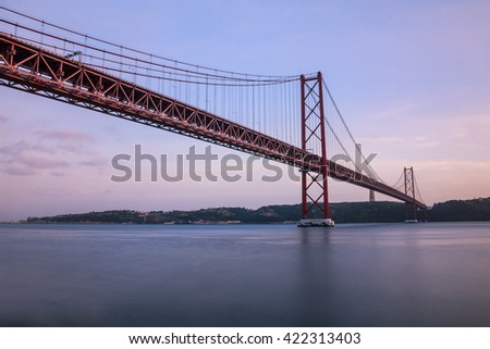 The 25 de Abril bridge over Tagus river and big Christ monument in Lisbon, Portugal, dawn at the famous lisbon 25 de Abril bridge #422313403