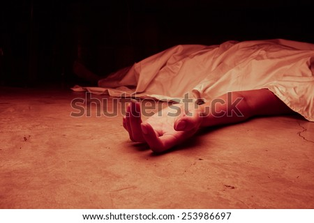 The dead woman\'s body. Focus on hand, red tone color processed