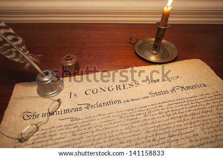 The Declaration of Independence with a candle holder, glasses and a quill pen