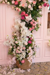 The decor of the cafe is a wicker basket entwined with flowers on the wall. Climbing plant. weaving flowers  roses on the facade of building on street. Fragment of building decorated with flowers