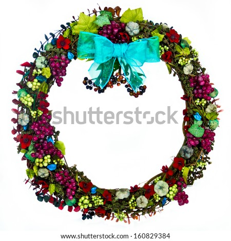 The decorations on a grapevine wreath are the colors of burgundy, green, blue-green, and dark blue and feature grapes, seed pods, husks, leaves, berries, flowers and eucalyptus with a blue-green bow.
