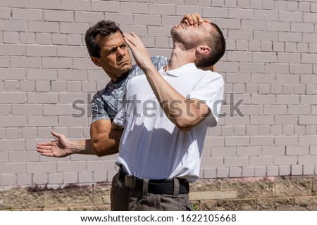 The defender performs a brutal technique, holding the attacker by the elbow. Close-up. Martial arts instructors demonstrate self-defense techniques of Krav Maga