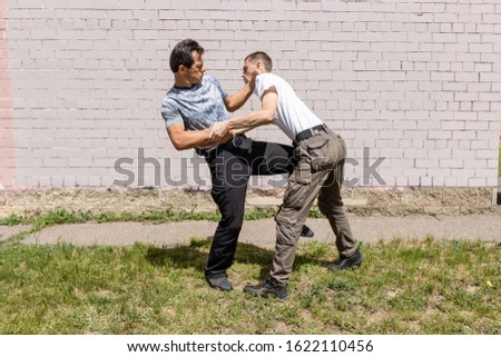 The defender performs a counter kick against the attacker, while fixing the hands of the attacker. Martial arts instructors demonstrate self-defense techniques of Krav Maga