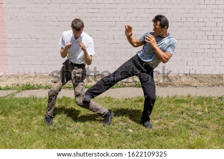 The defender performs a counter kick under the knee against the attacker. Martial arts instructors demonstrate self-defense techniques of Krav Maga