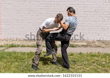 The defender performs a counter strike with a knee on the street. Martial arts instructors demonstrate self-defense techniques of Krav Maga