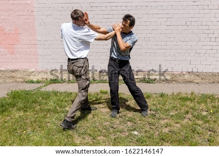 The defender performs a counter strike with a palm. Martial arts instructors demonstrate self-defense techniques of Krav Maga