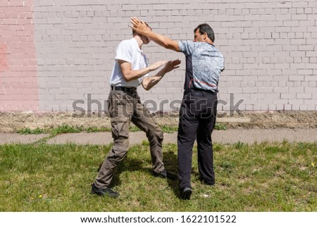 The defender performs a counter strike with a palm on the ear of the attacker on the street. Martial arts instructors demonstrate self-defense techniques of Krav Maga