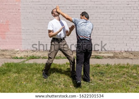 The defender performs a counter strike with the palm of his hand on the nose of the attacker on the street. Martial arts instructors demonstrate self-defense techniques of Krav Maga