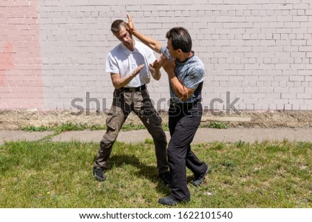 The defender performs a palm strike on the ear of the attacker on the street. Martial arts instructors demonstrate self-defense techniques of Krav Maga