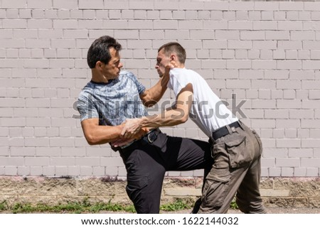 The defender strikes between the legs of the attacker, while fixing his hands. Martial arts instructors demonstrate self-defense techniques of Krav Maga