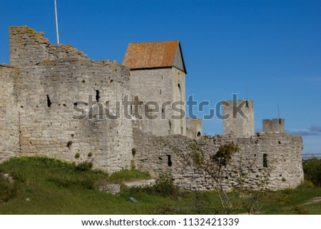 The defensive wall of Visby, Gotland in Sweden, is the strongest and best preserved medieval city wall in Scandinavia. Angular watchtowers and footpath along them. Blue sky on background, beautiful