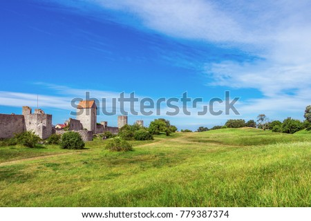 The defensive wall of Visby, Gotland in Sweden. Strongest and best preserved medieval city wall in Scandinavia. Beautiful view. Towers with orange tiled triangular rooftops, watchtower, green meadow.