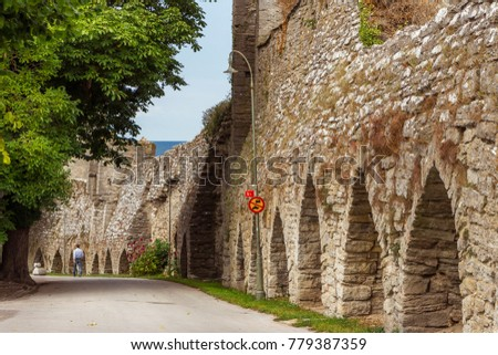The defensive wall of Visby, Gotland in Sweden. The strongest and best preserved medieval city wall in Scandinavia. Beautiful view. A road under the wall and arches with man going away in the distance