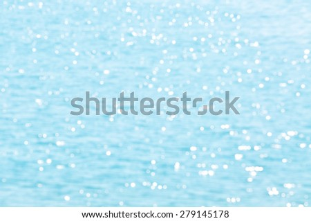 The Defocused Of Water surface with waves glittering in the sun. Out of focus bokeh of sun glares reflected