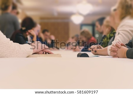 The delegation of people sitting at a long table. Visible only hands. Focus on the first hand, shallow depth of field.