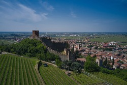 The delightful medieval town of Soave rises at the foot of the Lessinia Mountains. Soave castle aerial view, province of Verona, Italy. Aerial panorama of Italy castles.