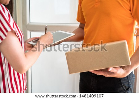 The delivery man waits to deliver the parcel while waiting for the woman to write a signature on the clipboard to confirm the receipt. #1481409107