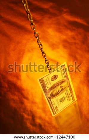 The denomination hundred dollar banknotes hangs on a chain on a gold background