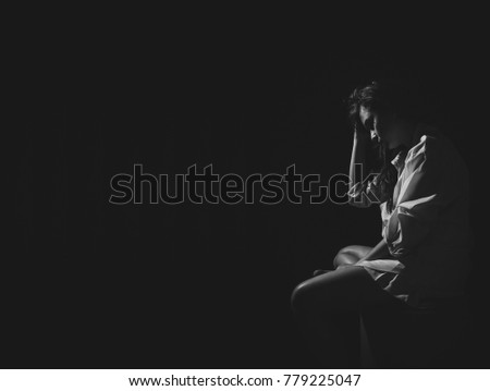 Photo of The depression woman sit on the chair on dark background, sad  asian woman silhouette in dark, monochrome image. Free from copy space.