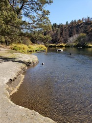 The Deschutes River in Central Oregon flows through Cline Falls State Park on a sunny fall day.