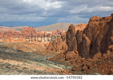 The desert of the Valley of Fire State Park beneath dramatic clouds.