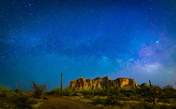 The desert wilderness of America's southwest grows dark at night as the sky lights up with brightly twinkling stars and the Milky Way shoots across the sky over iconic Superstition Mountains and cacti