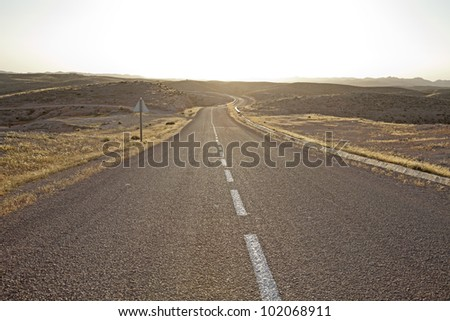 The desolated desert highway with a sharp bend at the end.