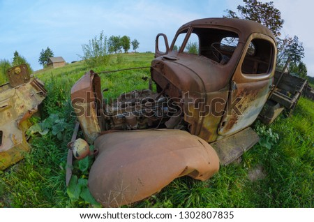 The destroyed wreck of a vintage military truck against the background of blue sky and field. #1302807835