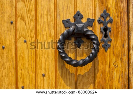 The detail of an old large oak door with iron pull and key hole hardware.